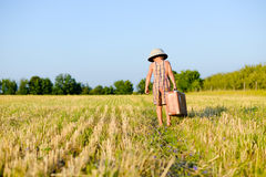 Niño pequeño que camina maleta vieja grande lejos que lleva Fotos de archivo libres de regalías