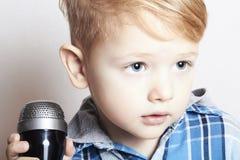 Niño pequeño que canta en microphone.child en karaoke.music Imagen de archivo libre de regalías