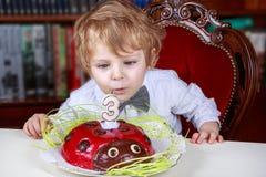 Niño pequeño que celebra el tercer cumpleaños y que descarga velas fotografía de archivo libre de regalías