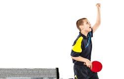 Niño pequeño que celebra la victoria sin defectos en los tenis de mesa aislados foto de archivo