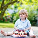 Niño pequeño que celebra su cumpleaños en el jardín del hogar con el Ca grande Foto de archivo libre de regalías