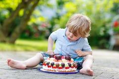 Niño pequeño que celebra su cumpleaños en el jardín del hogar con el Ca grande Foto de archivo