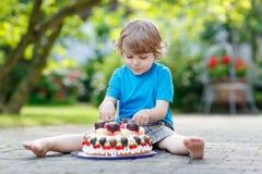 Niño pequeño que celebra su cumpleaños en el jardín del hogar con el Ca grande Imágenes de archivo libres de regalías