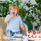 Niño pequeño que celebra su cumpleaños en el jardín del hogar con el Ca grande Fotografía de archivo libre de regalías