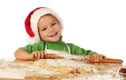 Niño pequeño que cocina la torta de la Navidad Foto de archivo libre de regalías