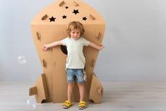 Niño pequeño que coloca el cohete cercano del cartón Imagenes de archivo