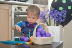 Niño pequeño que colorea los huevos de Pascua