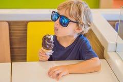 Niño pequeño que come el helado en un café fotos de archivo
