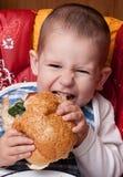 Niño pequeño que come la hamburguesa Fotos de archivo libres de regalías
