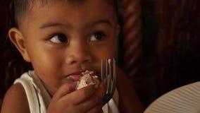 Niño pequeño que come la mano limpia del almuerzo en casa almacen de video