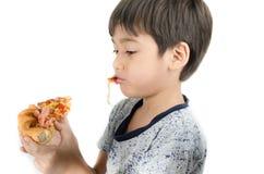 Niño pequeño que come la pizza en el fondo blanco Imágenes de archivo libres de regalías