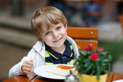 Niño pequeño que come la torta en café al aire libre Foto de archivo libre de regalías