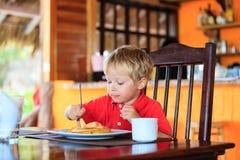 Niño pequeño que come las crepes en café Foto de archivo