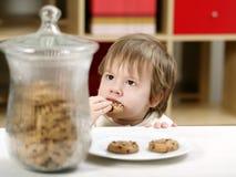 Niño pequeño que come las galletas Fotografía de archivo