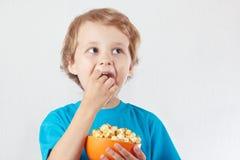 Niño pequeño que come las palomitas Fotografía de archivo libre de regalías