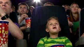 Niño pequeño que come las palomitas y que mira película en almacen de video