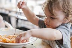 Niño pequeño que come las pastas Imagenes de archivo