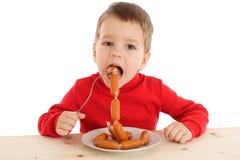 Niño pequeño que come las salchichas Fotografía de archivo