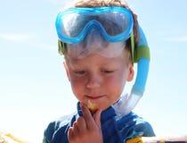Niño pequeño que come los vidrios y el schnorkel que se zambullen que llevan del bocado Fotografía de archivo