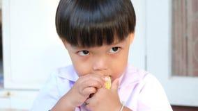 Niño pequeño que come maíz y que busca algo almacen de metraje de vídeo
