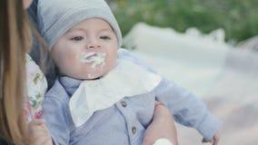 Niño pequeño que come un yogur en las manos del ` s de la madre metrajes