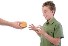 Niño pequeño que come una hamburguesa Fotografía de archivo libre de regalías