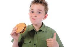 Niño pequeño que come una hamburguesa Imagenes de archivo