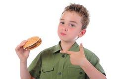 Niño pequeño que come una hamburguesa Fotos de archivo