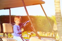Niño pequeño que conduce el carro de golf en la playa Imagenes de archivo