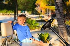 Niño pequeño que conduce el carro de golf en la playa del verano Fotografía de archivo