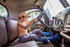 Niño pequeño que conduce un camión grande en el verano Fotografía de archivo