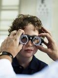 Niño pequeño que consigue sus ojos comprobados foto de archivo libre de regalías