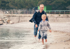 Niño pequeño que corre con su padre en la línea de la resaca Foto de archivo