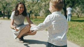 Niño pequeño que corre para mimar La mamá feliz abrió sus manos y bebé sonriente de la captura metrajes