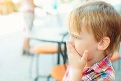 Niño pequeño que cubre su boca con sus manos, al aire libre fotos de archivo libres de regalías