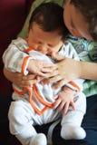 Niño pequeño que detiene y que acaricia a su hermana Foto de archivo libre de regalías