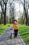 Niño pequeño que empuja su bicicleta en un parque Imágenes de archivo libres de regalías