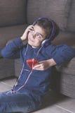 Niño pequeño que escucha la música Imagen de archivo