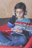 Niño pequeño que escucha la música Imagenes de archivo