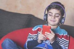 Niño pequeño que escucha la música Imágenes de archivo libres de regalías