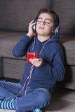 Niño pequeño que escucha la música Fotografía de archivo