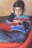 Niño pequeño que escucha la música Fotos de archivo