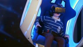 Niño pequeño que experimenta la realidad virtual que se sienta en silla móvil interactiva Fotos de archivo
