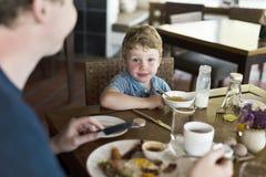 Niño pequeño que goza comiendo el desayuno imagenes de archivo