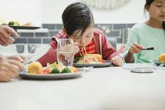 Niño pequeño que goza de su sofrito de los tallarines Foto de archivo libre de regalías