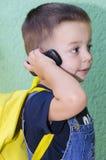 Niño pequeño que habla en móvil Imagenes de archivo