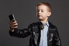 Niño pequeño que hace el selfie Niño divertido con un teléfono Pequeño fotógrafo Fotografía de archivo