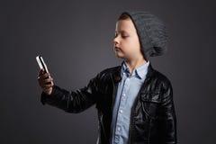 Niño pequeño que hace el selfie Niño divertido con un teléfono Pequeño fotógrafo Foto de archivo