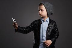 Niño pequeño que hace el selfie Niño divertido con un teléfono Pequeño fotógrafo Imagen de archivo