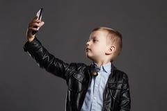 Niño pequeño que hace el selfie Niño divertido con un teléfono Pequeño fotógrafo Imagen de archivo libre de regalías